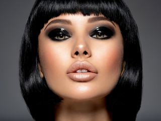 Beautiful fashion woman with a bob hairstyle looks to the camera.  Сloseup face of a sexy fashion model with black gloss make-up,  Attractive white girl with black eye-makeup.  Art. Papier Peint