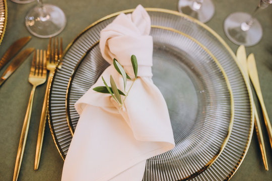 Banquet table served with glass plates with napkins, gold cutlery and glasses