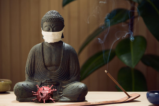 Masked Buddha contemplates covid-19 virus zen