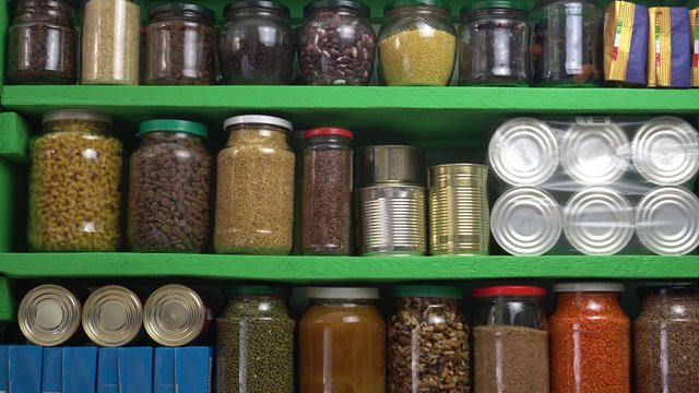 Stocked home pantry ready for coronavirus quarantine and self-isolation. Long storage foods, drinks, supplies. Dry beans, rice, pasta, popcorn, butter, nuts, seeds, canned goods and vegetables
