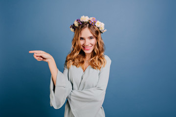 Wall Mural - Stunning fair-haired girl in flower wreath posing with playful smile. Studio shot of enthusiastic young woman in romantic attire expressing good emotions.