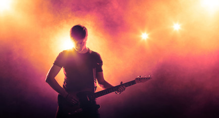 Silhouette of a guitar player on floodlighted stage