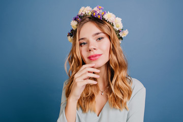 Wall Mural - Lovely european woman with pale skin posing on dark-blue background. Pretty white girl wears elegant flower wreath looking to camera.