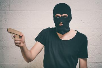 Face of burglar wearing a black ski mask or balaclava with a gun in his hand