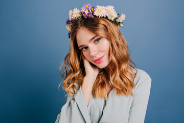 Wall Mural - Romantic blue-eyed girl with flowers in hair posing on dark background. Close-up indoor photo of wonderful caucasian woman touching her cheek.