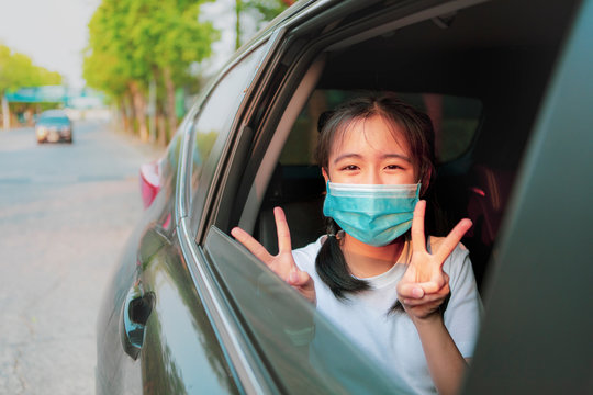 asian teenager wearing protection mask sitting in car hand sigh for victory