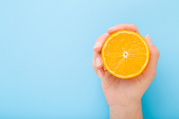 Young woman hand holding half of orange. Fresh fruit. Empty place for text on light blue table background. Pastel color. Closeup. Top down view. Wall mural