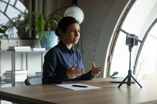 Focused young indian ethnicity businesswoman sitting at table in front of cellphone on stabilizer, recording educational video for personal vlog, sharing knowledge with followers online in office.