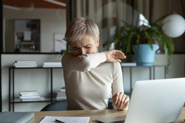 Front view young female manager with short haircut coughing or sneezing in elbow while working on...