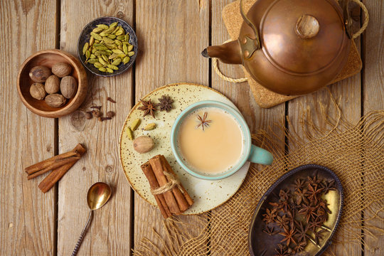 Masala chai tea traditional indian drink  with milk and spices on wooden background. Top view from above