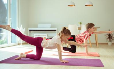 Happy children making yoga at home dueing coronavirus quarantine Wall mural