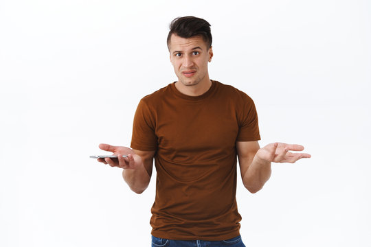 Technology, online lifestyle and people concept. What big deal, why so serious. Portrait of troubled and confused adult man shrugging with spread hands, hold mobile phone, cand understand