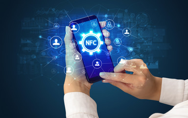 Female hand holding smartphone with NFC abbreviation, modern technology concept