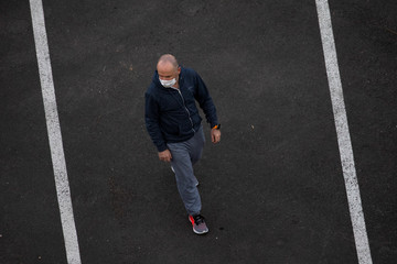 A man wears a face mask as he walks around his home amid the coronavirus disease (COVID-19) spread in Ashkelon