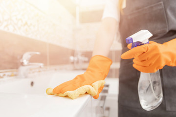 Woman disinfects surface of bathroom from viruses, germs dust and dirt. House cleaning