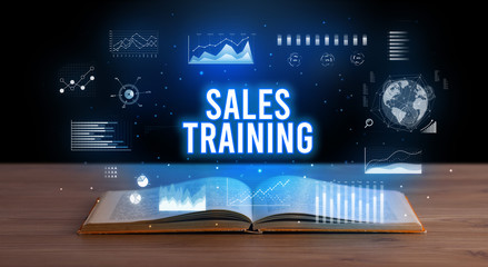 SALES TRAINING inscription coming out from an open book, creative business concept