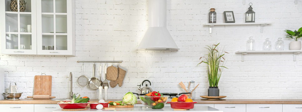 Modern stylish kitchen interior with vegetables and fruits on the table .