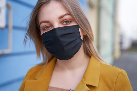 Young Caucasian European girl 20 years old wearing black protective medical mask protection against epidemic coronavirus covid-19