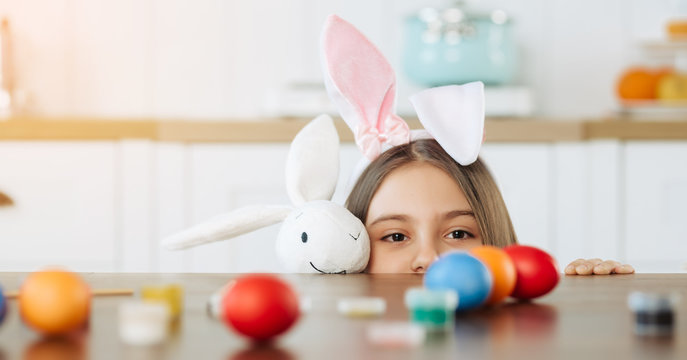 Small girl begin to hunt for Easter eggs. Happy family preparing for Easter. Cute little girl wearing bunny ears on Easter day.