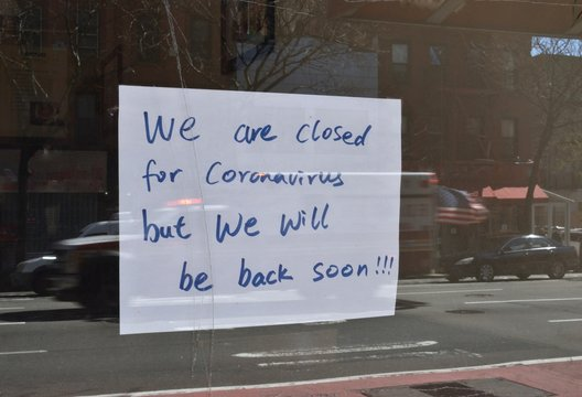 Handwritten sign reading We Are Closed For Coronavirus But We Will Be Back Soon!!! on a glass door with ambulance in reflection flying the American flag, April 4, 2020, in New York .
