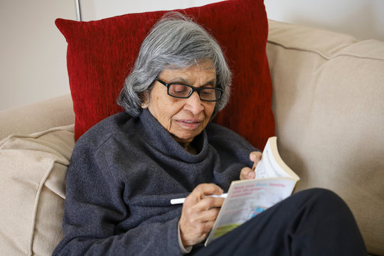 Old Asian woman with puzzle book, coronavirus self isolation UK