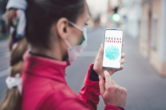 Woman using a phone with the coronavirus tracking app installed