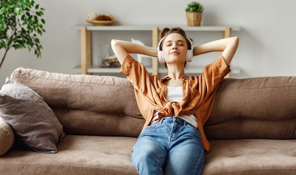 Pleased young woman in headphones listening to music while relaxing on sofa at home