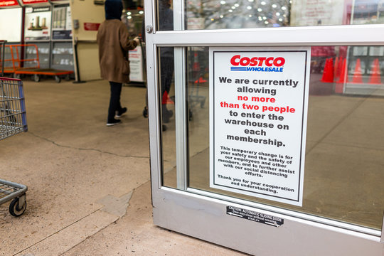 Sterling, USA - April 1, 2020: Costco warehouse club store social distancing sign with limit of two people to enter in shop per membership to prevent covid-19 coronavirus outbreak spread