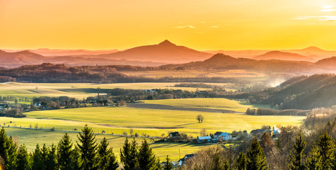 Self adhesive Wall Murals Orange Hilly landscape illuminated by evening sunset. Green grass fields and hills on the horizont. Vivid spring rural countryside. Ralsko Mountain, Czech Republic