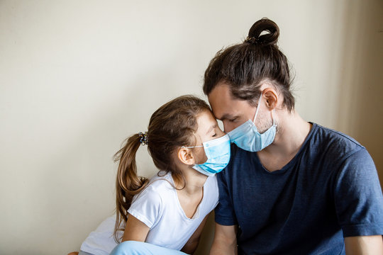 Stay at home family due coronavirus pandemic quarantine. Close up father and daughter in protective masks scrap to the forehead looking at each other. Family care and togetherness. Stay safe concept.