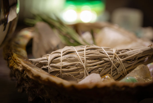 Closeup of Dried Tied Bundle of Organic White Desert Sage Native American Smudge Wiccan Smudge Stick In An Abalone Shell Surrounded by Herbs & Crystals