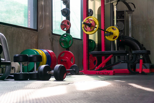 Lots of functional equipment in cross-training gyms, including squat racks, barbell weights, and a wide variety of equipment in colorful gyms.