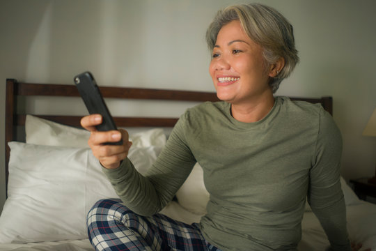 attractive and happy middle aged woman on her 50s using internet mobile phone in bed relaxed and cheerful online dating or enjoying social media app