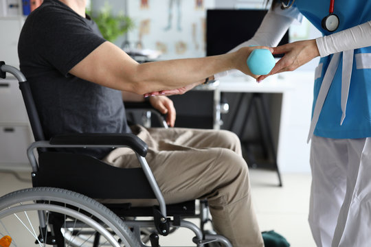 Female nurse helps lift dumbbell to disabled patient rehabilitation therapy concept. Process of recovering patients after severe injuries