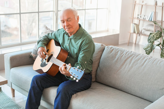 Elderly man playing guitar at home