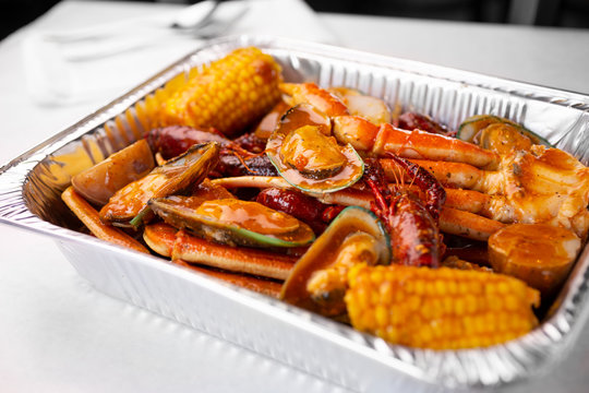 A view of a tin container of seafood boil, in a restaurant or kitchen setting.