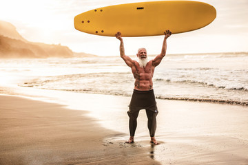 Tattooed senior surfer holding surf board on the beach at sunset - Happy old guy having fun doing extreme sport - Joyful elderly concept - Focus on his face Fotobehang