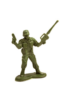 Simple dark green plastic toy soldier holding a pistol and a machine gun in hands, holding them up in a victory gesture Infantry figure object isolated on white, cut out Winning warfare concept symbol