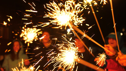 Happy friends burn out sparklers in the winter outside. They dance and laugh, the lights sparkle.