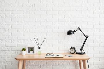 Modern stylish workplace near white brick wall