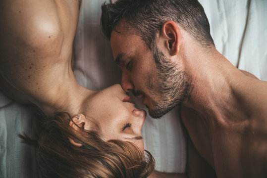 Sensual and romantic young couple kissing and making love on the bed at home. Love concept