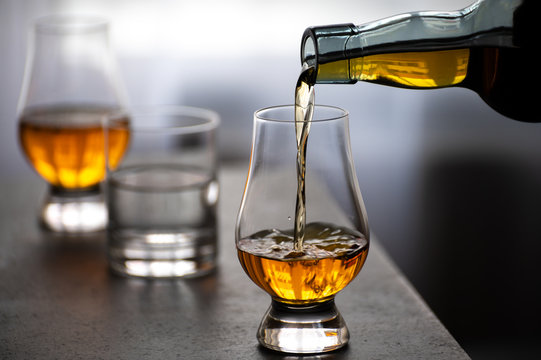 Pouring in tulip-shaped tasting glass Scotch single malt or blended whisky