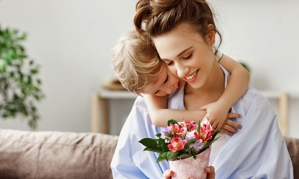 Little boy embracing happy woman with bouquet of colorful flowers.