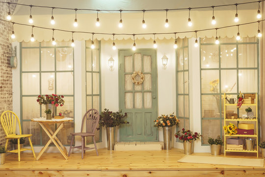 Summer porch with garlands of light bulbs. Terrace of summer house design of photo Studio. Patio verandah with flowers in metal buckets and wooden chairs and table. Street garland with light bulb