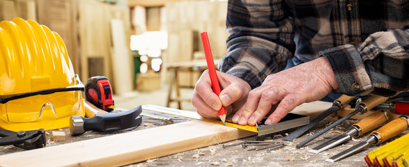 Close-up. Carpenter with pencil and carpenter's square draw the cutting line on a wooden board. Construction industry, carpentry workshop.