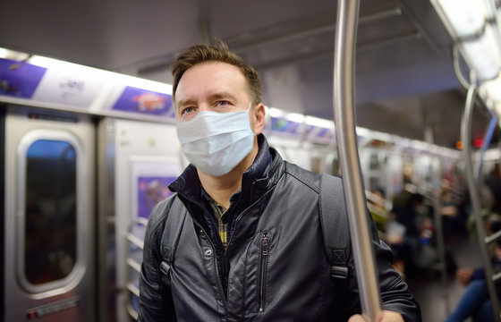Mature man wearing disposable medical face mask in car of the subway in New York during coronavirus outbreak.