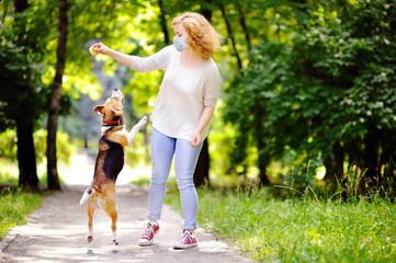 Young beautiful woman wearing disposable medical face mask playing with Beagle dog in the park during coronavirus outbreak. Walking of pets. Fotomurales