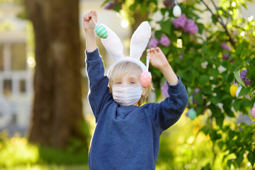 Pretty little boy wearing bunny ears and disposable medical face mask hunting for easter eggs in...