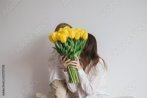 Boy child son congratulates mom with a bouquet of yellow tulips. Mother's Day, Women's Day. Birthday. Hug, laugh, happy.