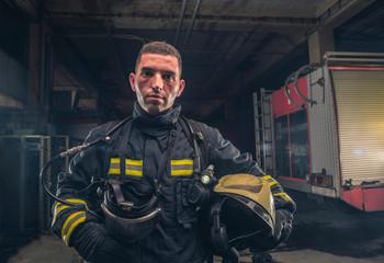 Portrait of a fireman wearing firefighter turnouts holding helmet ready for emergency service.